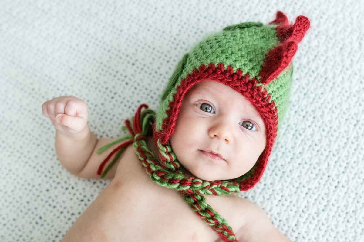 Littleton family and newborn baby photographer little boy in a dinosaur knit hat in home