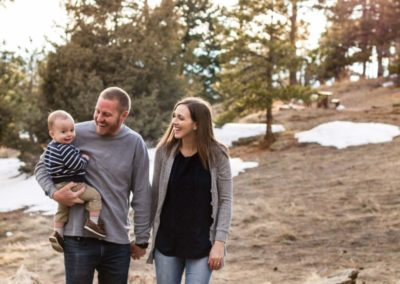 Littleton family photographer walking baby boy mother father son Mt. Falcon park Colorado mountains view mountain forest photography winter light snow spring sunset golden hour baby on the way