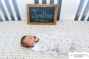 Littleton family photographer crib newborn new baby boy Jonathan swaddled sleeping content Colorado in home lifestyle session photo photos photography sign chalkboard nursery