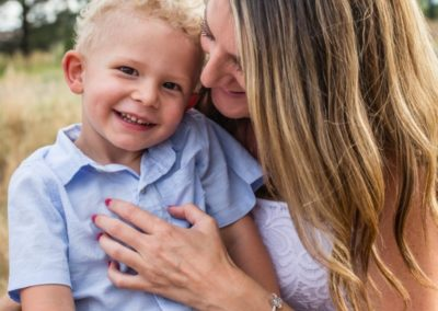 Littleton family photographer mother son bond Lakewood Heritage Center snuggles laughter candid moment real smile little boy Mommy's guy summer sunset light