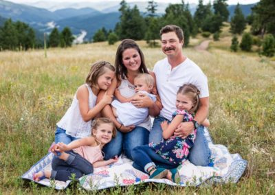 Littleton family photographer Mt. Falcon park in Colorado with a mountain view four girls sisters photography field summer mother father parenthood baby girl antique quilt