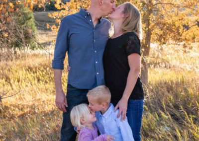 Littleton family photographer in Colorado Ken Caryl Valley foothills photography fall leaves kids brother sister siblings children kisses kissing parenthood marriage married love