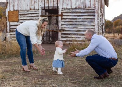 Littleton family photographer in Colorado baby girl walking to her Daddy first steps from Mommy one year old daughter Hildebrand Ranch barn fall
