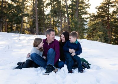 Littleton family photographer in Colorado winter snow mountain view brother sister little big natural light pine trees Mt. Falcon park love bond siblings mother father son daughter mom dad parenthood