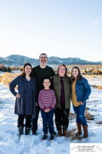 Littleton family photographer in Colorado Ken Caryl valley area three kids children big sister little brother siblings bond love foothills view snow winter natural light sun flare at sunset boy girls