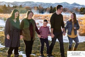 Littleton family photographer in Colorado Ken Caryl valley area three kids children big sister little brother siblings bond love foothills view snow winter natural light sun flare at sunset boy girls walking