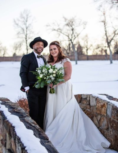 Littleton Colorado wedding photographer bride and groom stone bridge fedora hat snow winter Lakewood Country Club and golf course marriage married