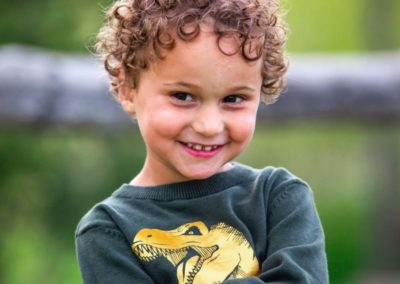 Littleton family photographer in Ken Caryl Valley foothills Colorado kids children little boy four years old candid real natural light curls dinosaur photo
