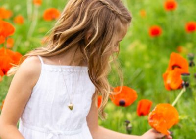 Littleton family photographer child children little girl flower wildflower field poppy poppies braids summer in Colorado Morrison