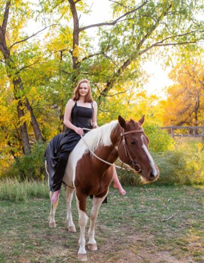 Littleton high school senior photographer Ken Caryl Valley equestrian center horse Chatfield girl painted dress twirling fall leaves red rocks rock formations bare back