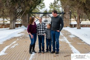 Littleton family photographer in Colorado at the Highlands Ranch Mansion in the snow boys brothers Christmas winter stone building iron gate