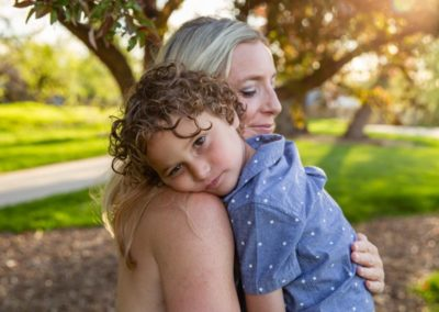 Littleton family photographer mother son snuggles spring in Colorado pink and white spring tree blooms blossoms sweet intimate candid moment sun flare sunset