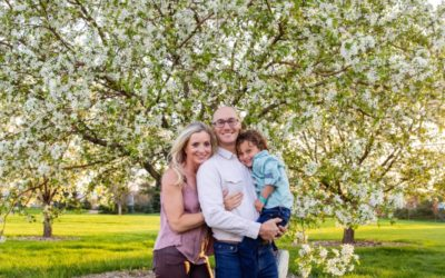 The {L} family of 3 in the crab apple tree blossoms for a spring photo session by Littleton photographer